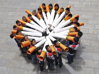 "Students pose for pictures with ""big cigarette models"" during a campaign ahead of the World No Tobacco Day, at a primary school in Handan, H"