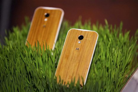 Phones with wooden backs on them rest in a display at a launch event for Motorola's new Moto X phone in New York, August 1, 2013. REUTERS/Lu