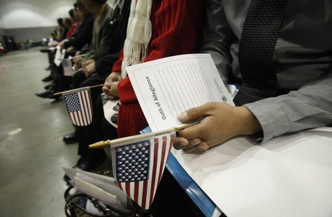 Candidates hold U.S. flags during a naturalization ceremony to become new U.S. Citizens at Convention Center in Los Angeles, California Febr