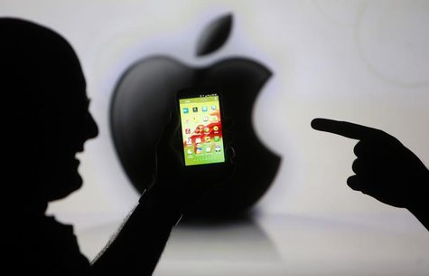 Men are silhouetted against a video screen with an Apple Inc logo as they pose with a Samsung Galaxy S3 smartphone in this photo illustratio