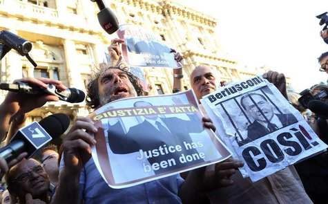 Two men hold up posters depicting former Italian Prime Minister Silvio Berlusconi during a protest in front of Italy's supreme court buildin