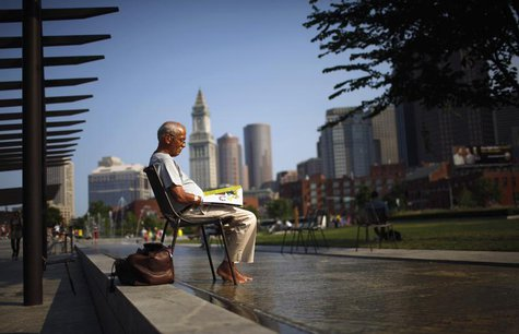 A man soaks his feet in a fountain while reading a magazine on the Rose Kennedy Greenway on a warm summer afternoon in Boston, Massachusetts