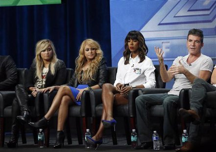 Judge Simon Cowell speaks next to fellow judges (from L-R) Demi Lovato, Paulina Rubio and Kelly Rowland at a panel for the television series