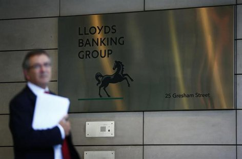 A man waits outside the corporate headquarters of Lloyds Banking Group in the City of London August 1, 2013.REUTERS/Andrew Winning