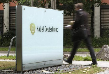 A man passes the company logo of German cable television group Kabel Deutschland in Unterfoehring north of Munich June 24, 2013. REUTERS/Mic