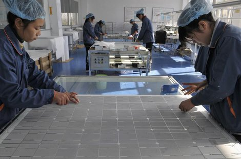 Employees work at the solar cells production line of the Blue Carbon Technology Inc. in Rizhao, Shandong province December 3, 2010. REUTERS/