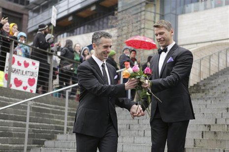 Seattle gay-rights advocate and journalist Dan Savage (L) and Terry Miller sort through roses on the steps of City Hall after getting marrie