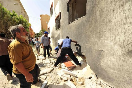 People gather to look at the damage caused by a bomb explosion at a police station in Benghazi August 2, 2013. REUTERS/Esam Omran Al-Fetori