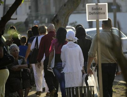 People walk in line to apply for visas at the U.S. diplomatic mission in Cuba, The United States Interests Section, (USINT), in Havana Febru