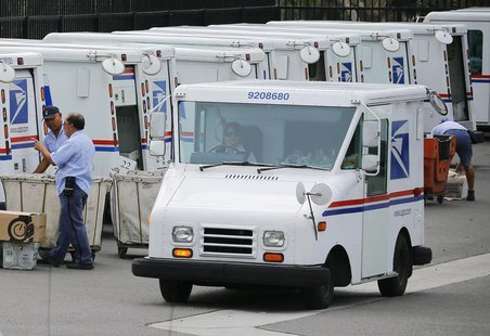 U.S. postal workers load their trucks with mail for delivery from their postal station in Carlsbad, California February 6, 2013. REUTERS/Mik