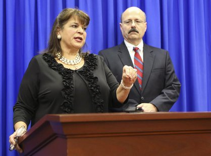 State Attorney Angela Corey and her assistant state attorney Bernie de la Rionda (R) address the media following the not guilty verdict for