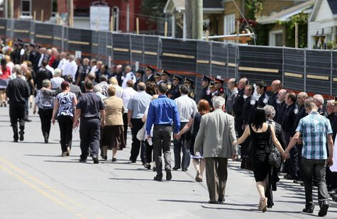 Mourners walk the perimeter of the red zone as rescue workers line the streets following a memorial service to honour the victims of the tra