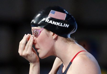 Missy Franklin of the U.S. adjusts a clip in her nose before competing in the women's 200m backstroke semi-final during the World Swimming C