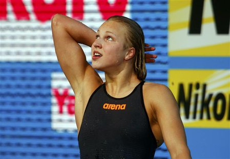 Lithuania's Ruta Meilutyte looks at the scoreboard after setting a new world record in the women's 50m breaststroke semi-final during the Wo