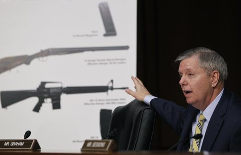 U.S. Senator Lindsey Graham (R-SC) points at a chart showing an (bottom to top) AR-15 semi-automatic rifle, a 12 gauge shotgun and a 15-roun