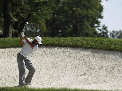 Tiger Woods of the U.S. hits his second shot from the sand on the 14th hole during the third round of the WGC-Bridgestone Invitational golf