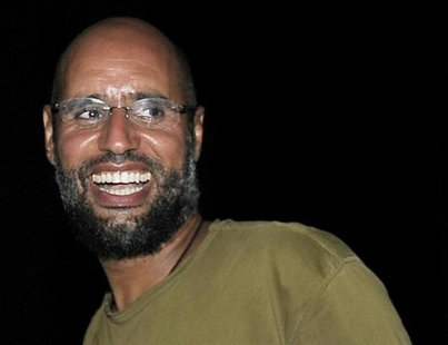 Saif al-Islam, the son of Libyan leader Muammar Gaddafi, smiles as he greets supporters in Tripoli in this August 23, 2011 file photo. REUTE