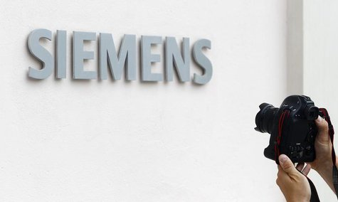 A photographer takes a picture of the Siemens logo at Germany's Siemens AG headquarter during board member meeting in Munich July 31, 2013.