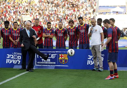 Israel's President Shimon Peres (L) kicks the ball to Barcelona's Lionel Messi (R) at the opening of a soccer clinic with Arab and Jewish ch