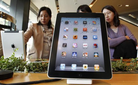 Visitors look Apple iPad 2 tablets, behind another iPad 2 on display, at a registration desk at South Korean mobile carrier KT's headquarter