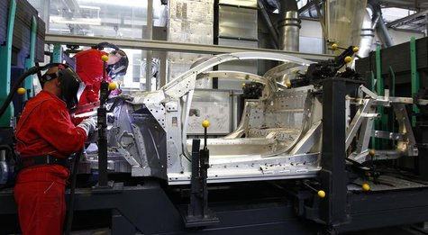 Workers assemble a new Audi R8 car body in the automotive welding and assembly lines hall of the German car manufacturer's plant in Neckarsu