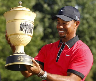 Tiger Woods of the U.S. holds the trophy after winning the WGC-Bridgestone Invitational golf tournament in Akron, Ohio, August 4, 2013. REUT