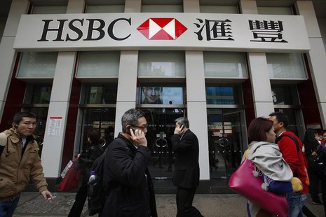 People walk outside one of the branches of HSBC in Hong Kong March 4, 2013. REUTERS/Bobby Yip