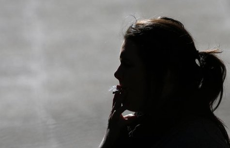 A woman is silhouetted as she smokes a cigarette in central Sydney August 1, 2013. REUTERS/Daniel Munoz
