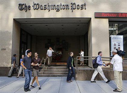 A television cameraman takes up a position as people walk by the entrance of the Washington Post headquarters in Washington, August 5, 2013.
