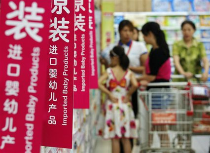 Customers talk to a sales assistant as they shop for milk powder in front of shelves displaying imported baby products at a supermarket in B