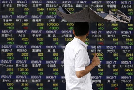 A pedestrian holding an umbrella walks past a stock quotation board displaying various stock prices outside a brokerage in Tokyo July 29, 20
