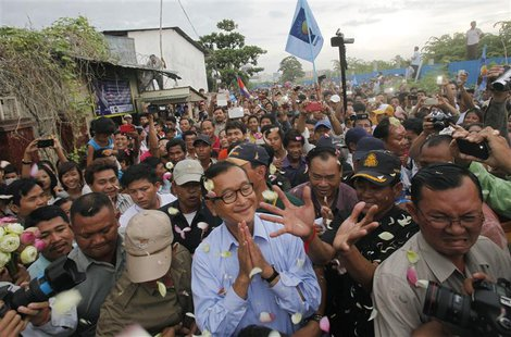 Sam Rainsy (C), president of the opposition Cambodia National Rescue Party (CNRP), greets supporters during a visit to the Boeung Kak lake a