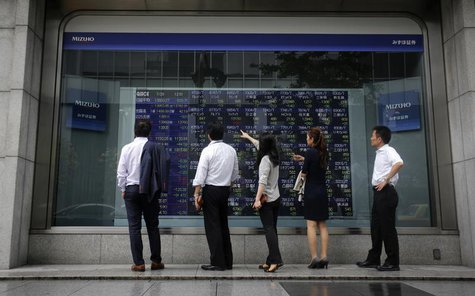 Pedestrians stand in front of a stock quotation board displaying various stock prices outside a brokerage in Tokyo July 29, 2013. REUTERS/Yu