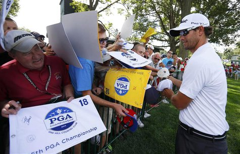 Australia's Adam Scott signs autographs during a practice round for the 2013 PGA Championship golf tournament at Oak Hill Country Club in Ro