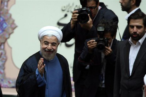Iran's new President Hassan Rouhani (L) gestures as he arrives to his swearing-in ceremony at the Iranian Parliament in Tehran in this Augus