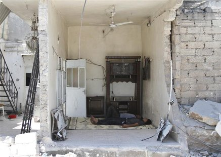 Men sleep inside a house damaged after what activists said was an air raid by forces loyal to Syria's President Bashar al-Assad in Azaz, nea