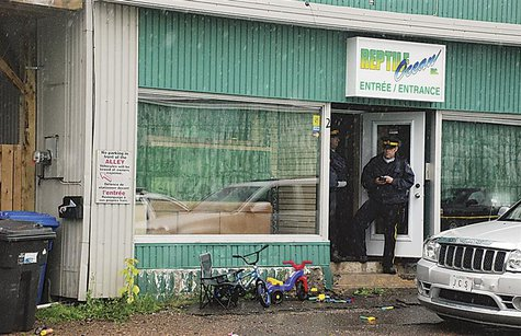 Police stand in front of the Reptile Ocean store in Campbellton, New Brunswick August 5, 2013 after an incident in which an African rock pyt