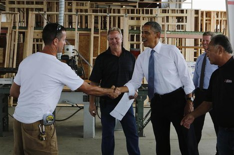 U.S. President Barack Obama (center R) is greeted as he looks at building supplies while touring Erickson Construction in Chandler, Arizona,