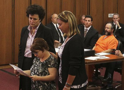 Michelle Knight (2nd from left) reads statements while supported by her attorney (L) and friend as her accused assailant Ariel Castro (R) si