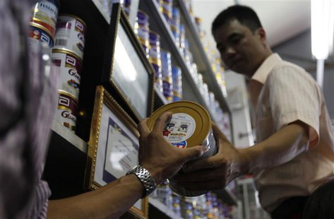An Abbott Laboratories sales staff hands over a powder milk tin during a production recall at a milk shop outside Hanoi August 6, 2013. REUT