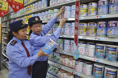 Chinese commercial law enforcement personnel inspect milk powder products at a supermarket in Lianyungang, Jiangsu province August 6, 2013.