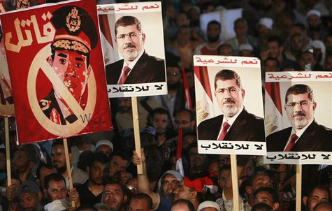 Supporters of deposed Egyptian President Mohamed Mursi hold up posters, including Egypt's army chief General Abdel Fattah al-Sisi (L) that r