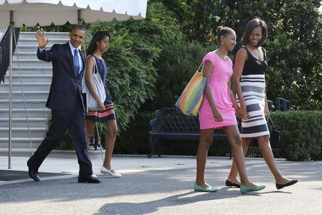 U.S. President Barack Obama (L) waves as he and his wife Michelle (R) and daughters Malia (2nd L) and Sasha (2nd R) depart for travel to Afr