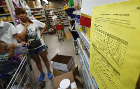 A woman looks at a notice about the product recall of some of Dumex and Abbott's milk powder products at a supermarket in Beijing August 7,