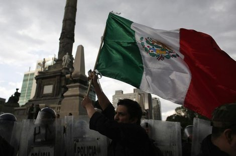 A demonstrator holds a Mexican national flag in front of riot policemen during a protest against the privatization of the state oil monopoly