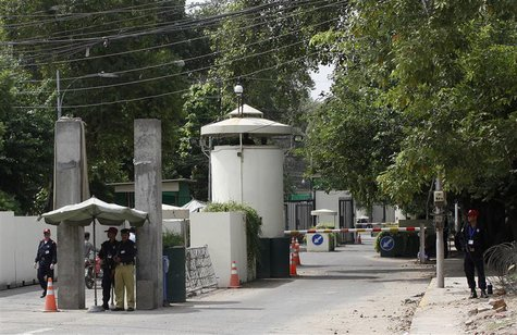 A policeman (2nd R) and private security personnel stand guard at the entrance of a road leading towards the U.S. consulate in Lahore August