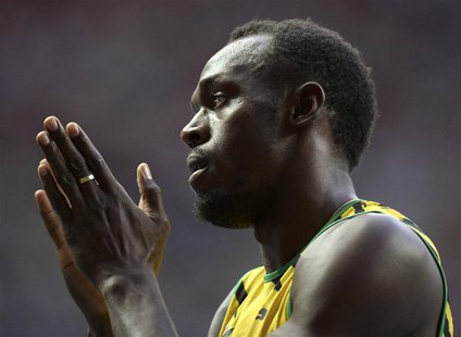 Usain Bolt of Jamaica applauds after winning his men's 100 metres heats during the IAAF World Athletics Championships at the Luzhniki stadiu