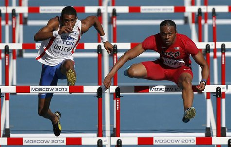 Aries Merritt of the U.S. (R) clears a hurdle next to Orlando Ortega of Cuba in the men's 110 metres hurdles heats during the IAAF World Ath