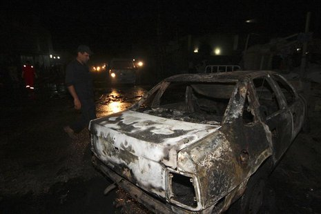 An Iraqi security force personnel inspects the site of a car bomb attack in Kerbala, 110 km (68 miles) south of Baghdad, August 10, 2013. RE