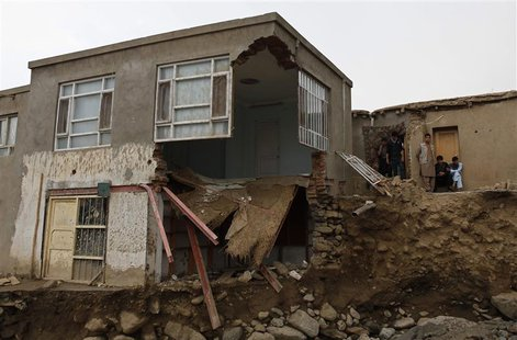 Afghans stand near a destroyed house after floods in the Shakar Dara district of Kabul August 11, 2013. REUTERS/Mohammad Ismail